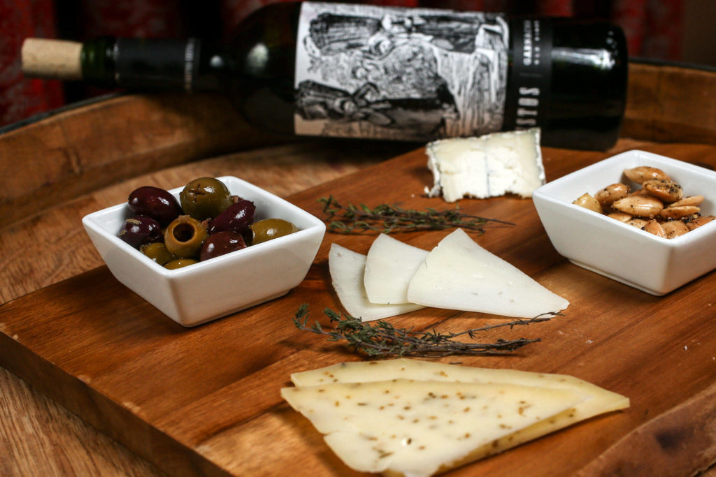 A goat and gouda cheese plate with marcona almonds and kalamata, picholine and cerignola olives, paired with Zestos granacha wine, is one of Greg Claus's favorite pairings. (Kevin Clark / The Herald)