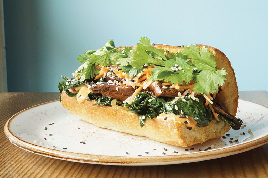 Stacked Sandwich Shop borrows the popular banh mi flavor profile and spins it into a Portobello Banh Mi with sautéed kale, pickled carrot, daikon radish and cilantro, served in a toasted hoagie.