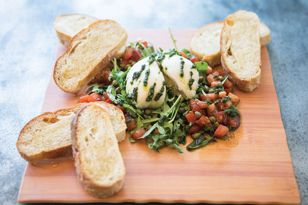 """Fare Well in Washington, D.C., menus a vegan burrata """"cheese"""" made with cashew milk, almonds, lactic acid and the magic of time. It's paired with pesto, balsamic-marinated tomatoes, capers, arugula and a toasted baguette."""