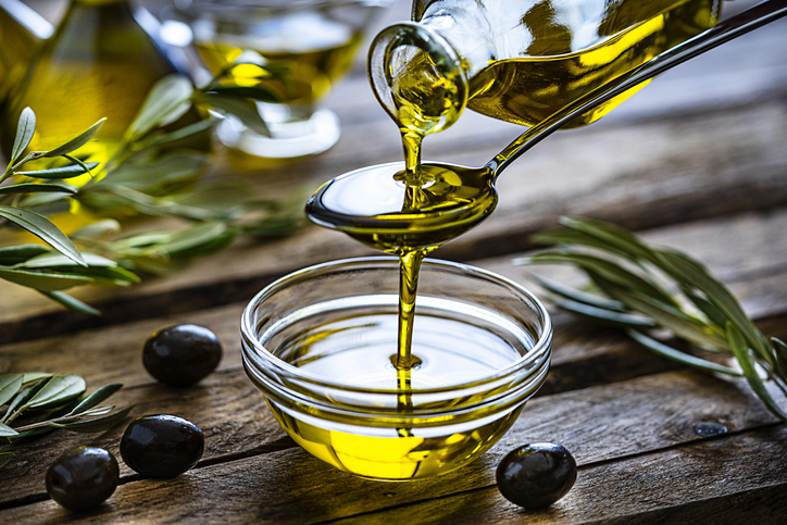 Pouring olive oil in spoon and glass bowl