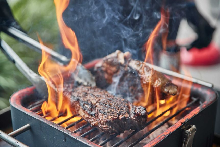 Beef being cooked on a flaming grill.