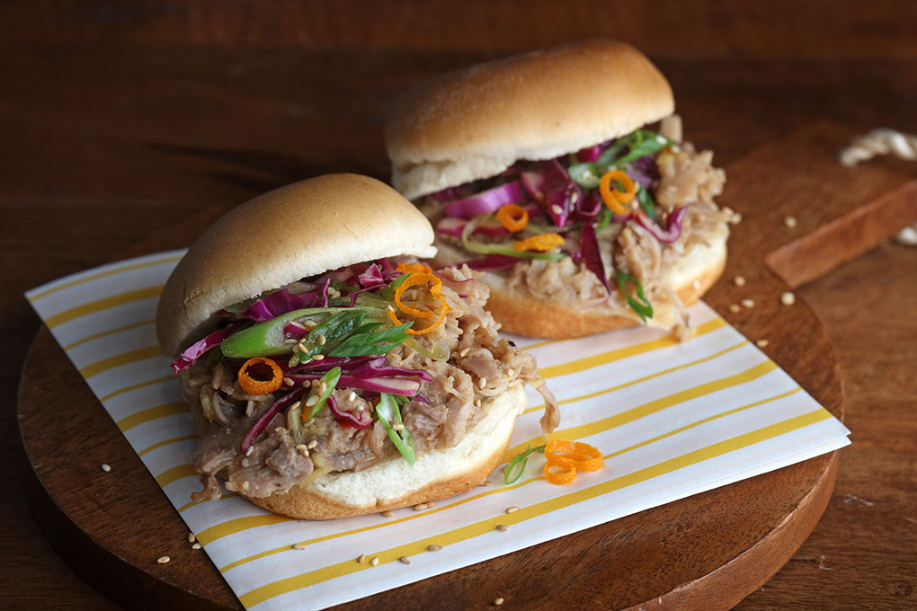 Orange Pepper Pulled Pork Sliders celebrate the craveable flavors of the classic orange sauce, making a bright-hot version and featuring it on these Orange Pepper Pulled Pork Sliders. A crisp and colorful Greens Slaw adds crunch.