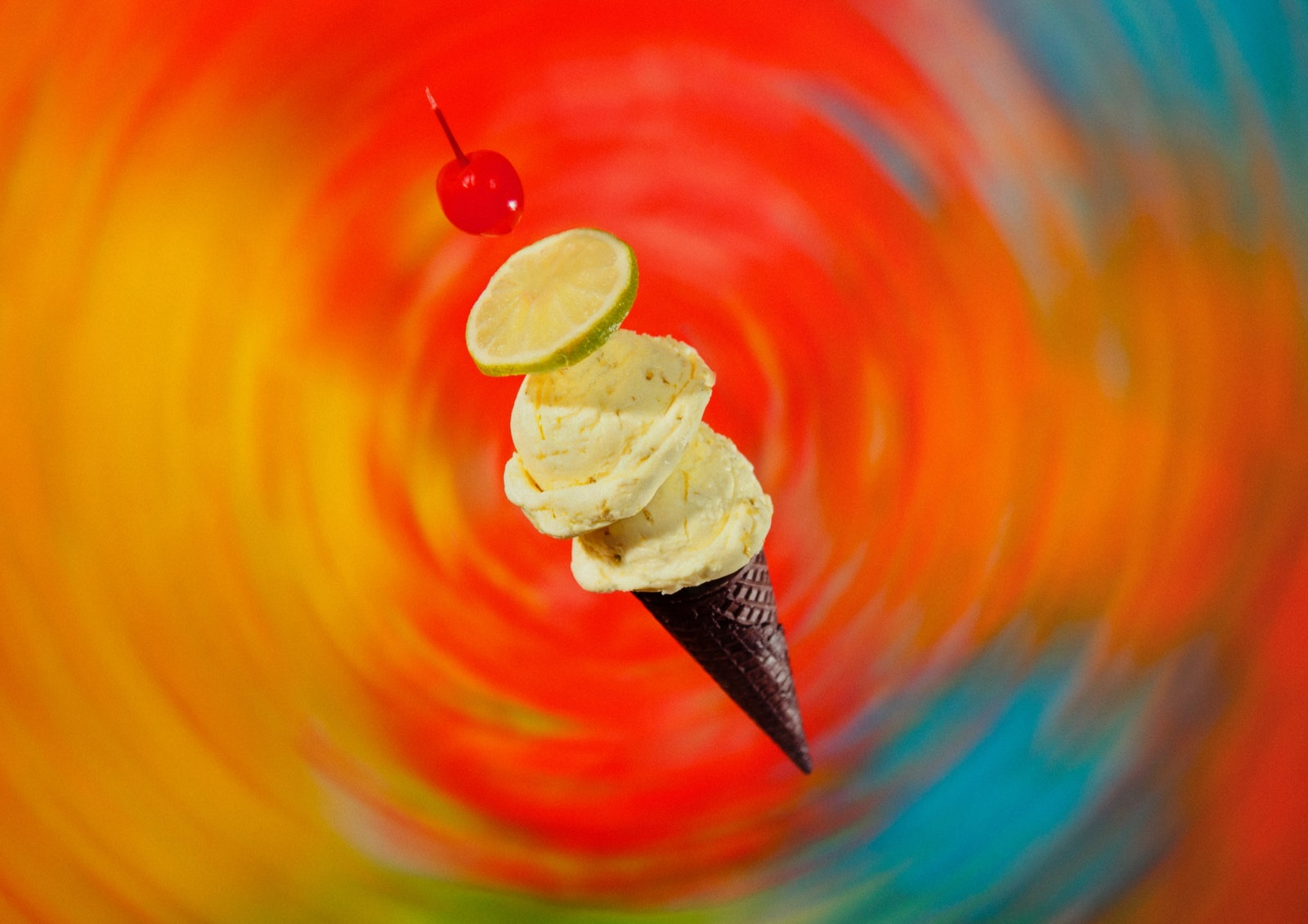 Ice cream cone with a lime and a cherry.
