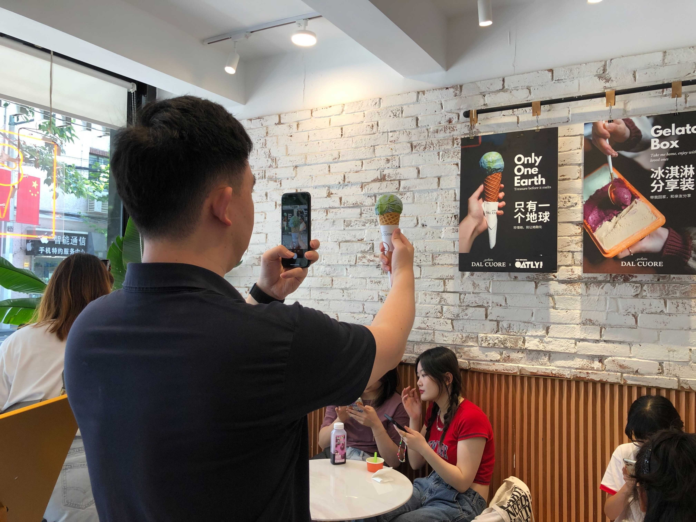 A man holds up a cone with blue and green ice cream as he takes a photo of it against a poster